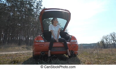 a girl sits in the trunk on the nature