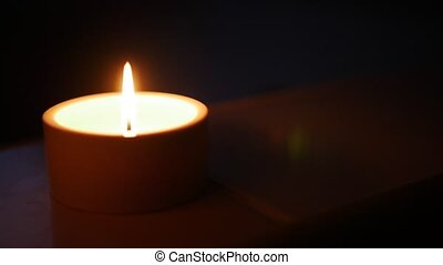 Close-up of a candle in the dark, shallow depth of field with focus on the wick and flame.