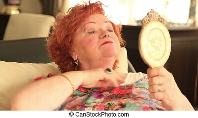 Senior woman looking at her skin in mirror - Senior woman...