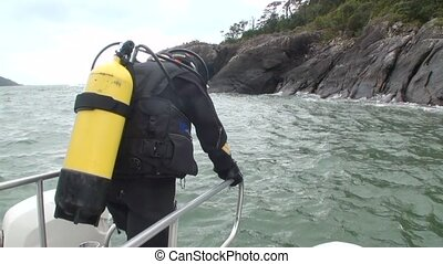 Diver descends into the ocean from the boat in New Zealand....