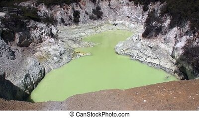 Geysers green water hot springs on background of soil in New...