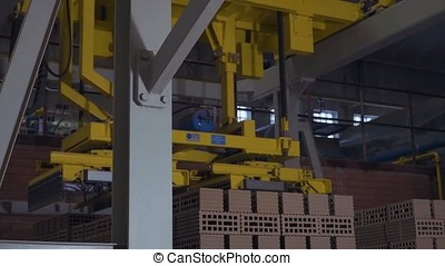 Plant for the production of bricks. Plant for production building material with ready brick, construction industrial. Production of bricks on plant. Workflow, close-up. Many bricks
