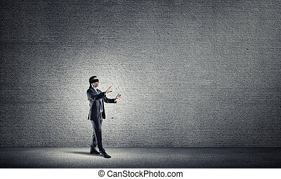 Business concept of risk with businessman wearing blindfold in empty concrete room