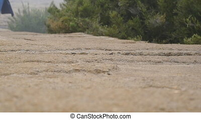 Female foot running on stone trail outdoor. Legs of woman...