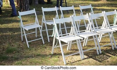 Wedding setup in garden, park. Outside wedding ceremony, celebration. Wedding aisle decor. Rows of white wooden empty chairs on lawn before the wedding ceremony. Slow pan.