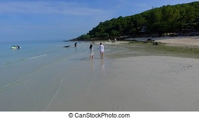 Couple walking on beach. Young happy interracial couple walking on beach smiling holding around each other. Senior couple holding hands at the beach on a sunny day. Mature couple in love