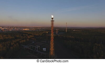 a tower with a torch on a oil refinery among the woods at sunset. Aerial view
