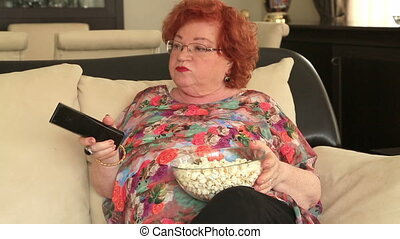Woman watching tv, eating popcorn