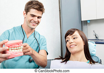 Dental Clinic Patient - Male dentist explaining a female...