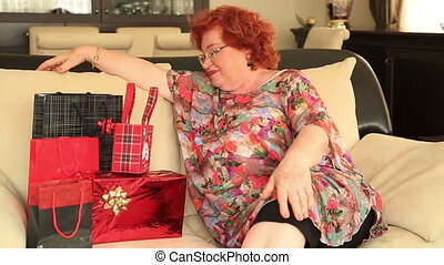 Woman with pile of gifts - Happy red head, senior woman with...