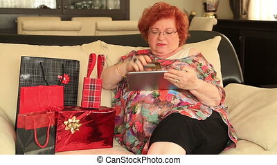 Woman with pile of gifts - Senior red head woman with lots...