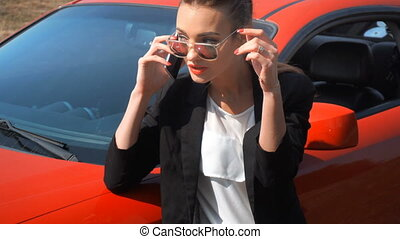 business Lady in glasses on the phone near the car