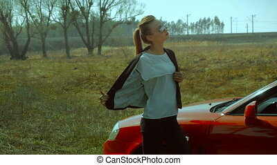 girl takes off the jacket near red car in the field -...