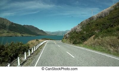 Serpentine road on ocean coast panorama view from car window in New Zealand.