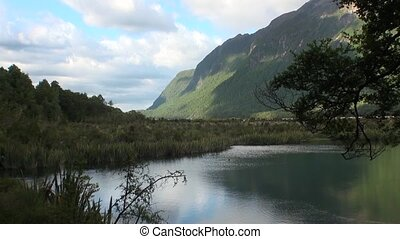 Unique lake in green mountains calm water of New Zealand.