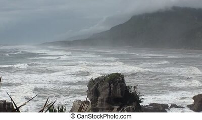 Waves on a rocky coast and mountains New Zealand.