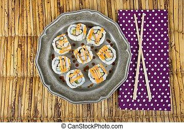 sushi pinwheel on pewter plate with chopsticks