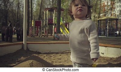A kid playing in a sandbox - A kid playing in sandbox on a...
