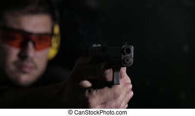 Shooting a gun on black background - Aiming and shooting a...