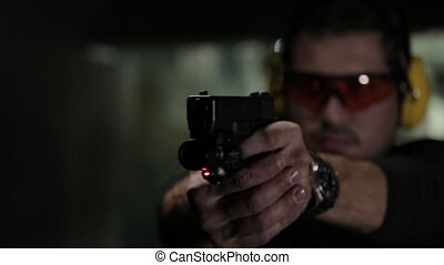 Shooting a gun with red aiming laser beam - pistol shooting...