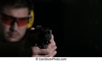 Aiming a gun with copy space - Holding a pistol over black...