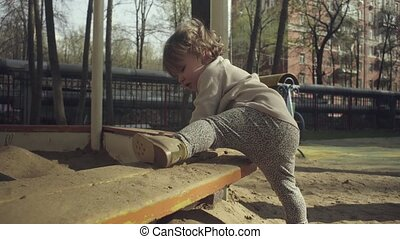 A kid trying to climb into a sandbox on a playground in a...