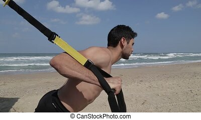 Side view work out with fitness straps - Young man exercise...