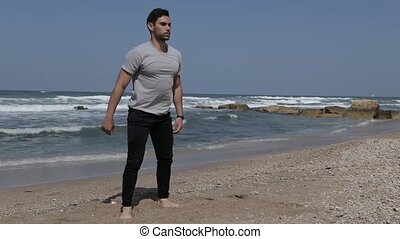 Man doing squat exercise on the beach - Man doing squat...