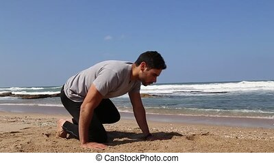 Man doing static plank exercise on the beach