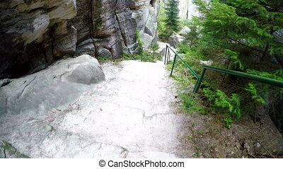 Walk down the stone stairs between rocks. - Walk down the...