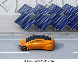 Orange electric car driving on the highway. Solar panel...