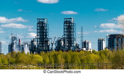 Oil refinery with pipes and distillation complexes with trees in the foreground and floating clouds in the background. Time lapse