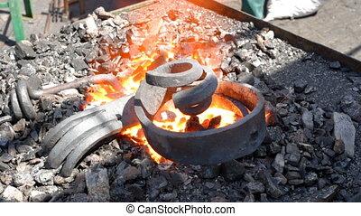 blacksmith heats metal - blacksmith working with molten iron...