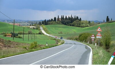 car on a road through the tuscanian hills