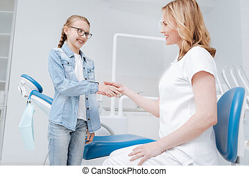 Enthusiastic teenage girl shaking hands with her doctor