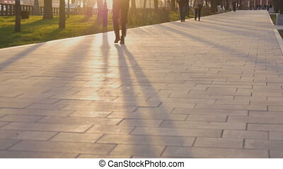 People go on a city street in sunset