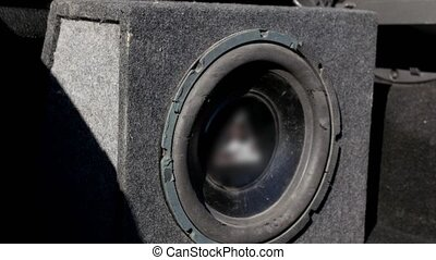 A black vibrating old ragged working subwoofer in car, close...