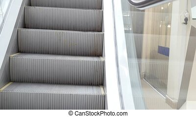 Moving staircase running down - escalator stairs, close up