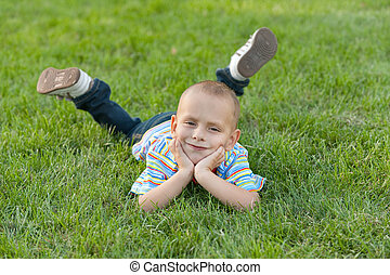 Kid on the grass - A  happy boy is lying on the green grass