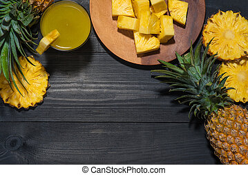 Top view of glasses of pineapple juice and pineapple fruit on a black wooden table