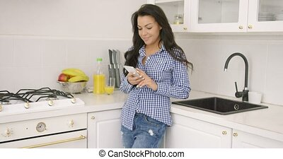 Young casual woman with smartphone in kitchen - Beautiful...
