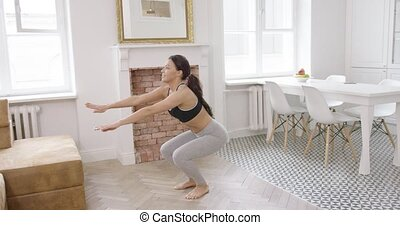 Fit woman working out at home - Young female wearing...