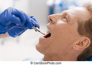 Handsome fit man undergoing dental examination in clinic