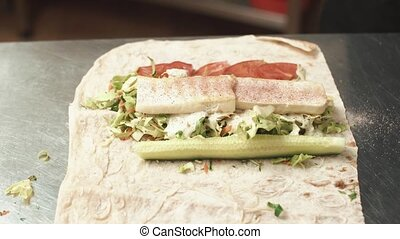 Man rolls vegetables and meat in the pita.