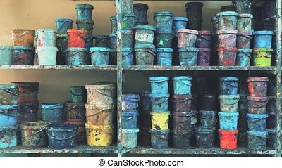 Industrial paint warehouse. Colorful stained buckets on the...
