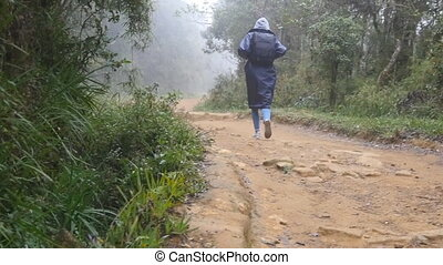 Young girl in raincoat jogging on wood trail during travel....