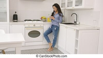 Fit young female using phone in kitchen - Side view of...