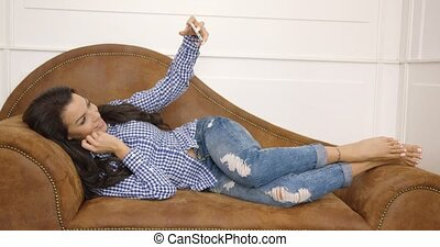 Young female taking selfie on couch - Young and beautiful...
