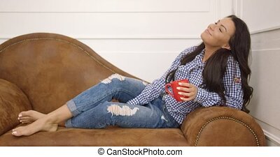 Young woman with mug on sofa - Beautiful young brunette in...