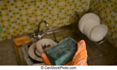 Sponge for washing dishes and gloves. - Dishwashing liquid...
